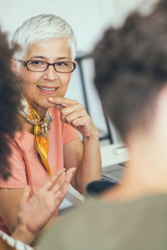 Smiling aged businesswoman looking listening to colleague at team meeting